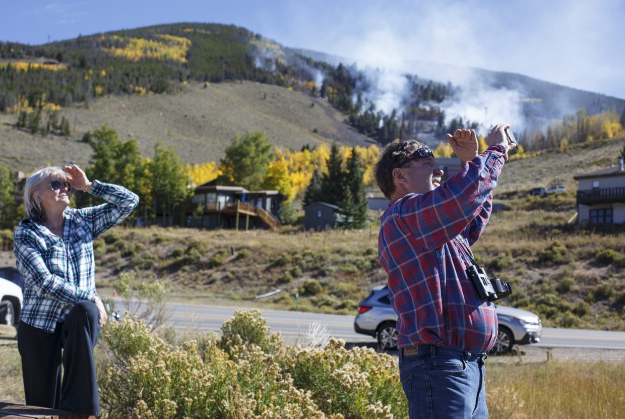Silverthorne residents Marleen Goodman, left, and Dan Moroz take photos of helicopter action along Highway 6 of the Tenderfoot 2 Fire Tuesday, Sept. 19, in Dillon.