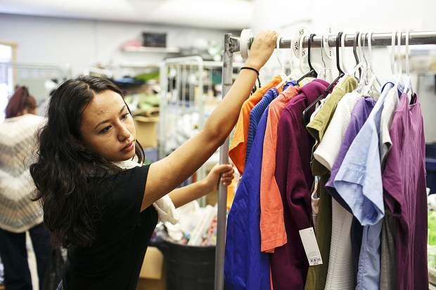 Ingrid Gaspar pushes a rack of clothes for sale in the Family & Intercultural Resource Center thrift store during her shift Thursday, Sept. 7, in Dillon.