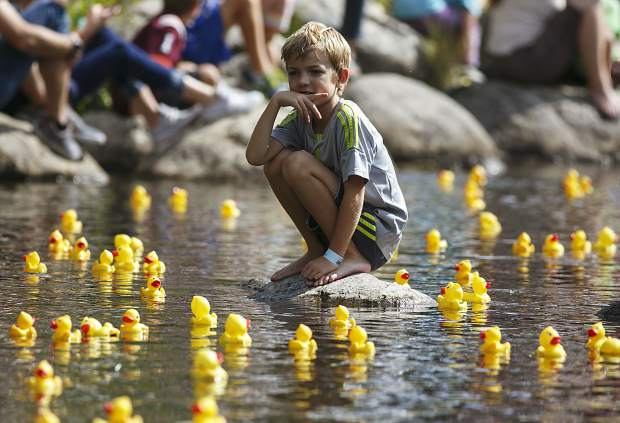 A young spectator watches thousands of rubber ducks float down the Blue River Saturday, Sept. 2, in Breckenridge.