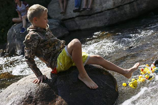 A young spectator help unstuck a few rubber ducks as it float down the Blue River Saturday, Sept. 2, in Breckenridge.