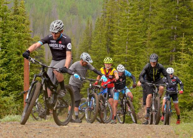 A small crew of local and visiting mountain bikers turns off of Turk's Trail and onto Sallie Barber Road in the French Creek trail system outside of Breckenridge, Colorado.