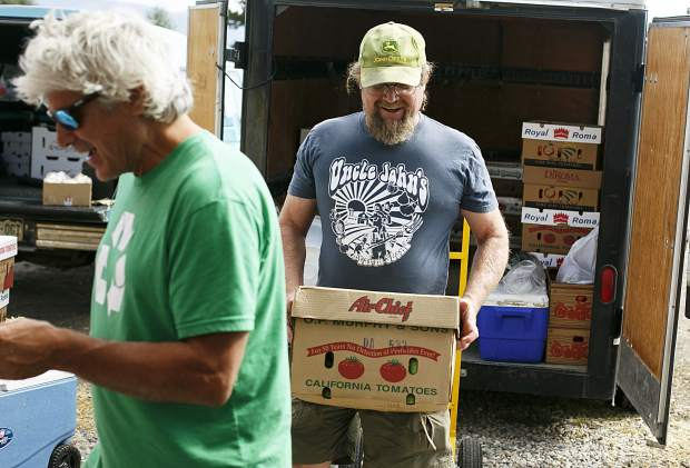 Uncle John's Farm Stand owner Chris Brower delivers fresh produce at the selling booth in Frisco Saturday, Sept. 9.