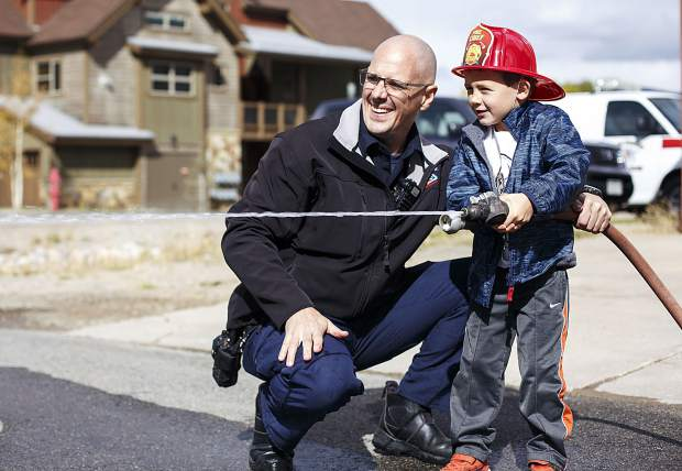 Lake Dillon Fire-Rescue firefighter Jason Bell assists Evan Boller, 5, with the fire hose interactive activity during the Ice Cream Social Saturday, Sept. 30, at the station in Frisco.