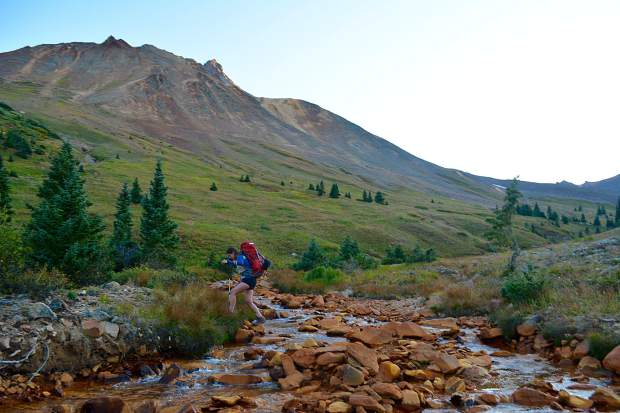 Forging a copper-colored stream on the approach to camp underneath the shadow of Uncompahgre Peak, Colorado's sixth highest 14,000 foot peak.