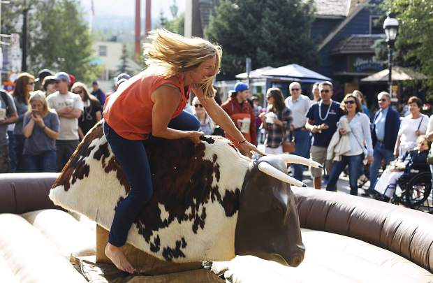 Colorado Weliever hangs on to the bull on Main Street during the Breckenridge Oktoberfest event Friday, in Breckenridge.