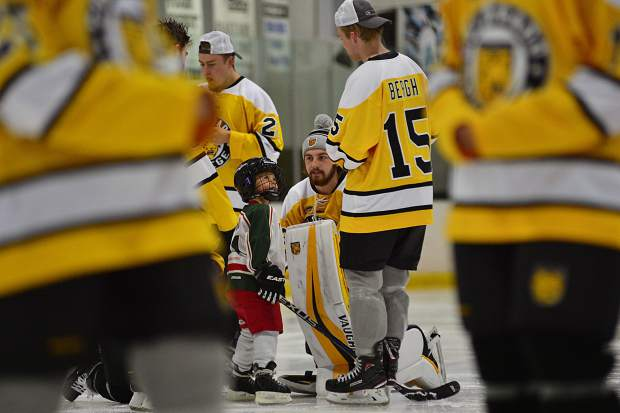 Case Conway, 5, looks up to Colorado College team captain Mason Bergh (15) while getting some advice from goalie Jon Flakne (center) during a Skate with the Tigers event Friday at the Stephen C. West Ice Arena. The NCAA Division I hockey team played an exhibition game against the University of Lethbridge, Alberta, Canada, in Breckenridge on Saturday and participated in the community event the night before.