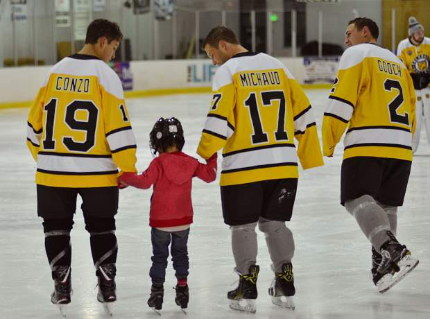 Hanna Goldstein holds hands as she skates with Colorado College hockey players Troy Conzo (19) of Nesconset, New York; Westin Michaud (17) of Cloquet, Minnesota; and Trevor Gooch (2) of Mantua, New Jersey, during a Skate with the Tigers community event Friday at the Stephen C. West Ice Arena.