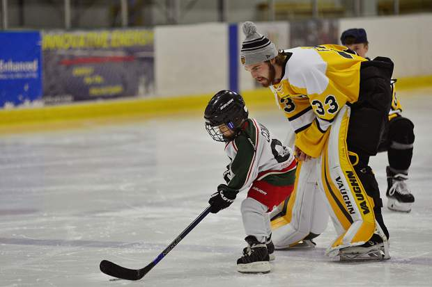 Five-year-old Case Conway takes instruction from Colorado College's 6-foot-2, 205-pound goalie Jon Flakne of Maple Plain, Minnesota, during a Skate with the Tigers event Friday at the Stephen C. West Ice Arena. The NCAA Division I hockey team played an exhibition game against the University of Lethbridge, Alberta, Canada, in Breckenridge on Saturday and participated in the community event the night before.