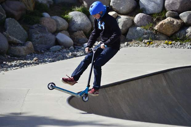 Jacob Rowe, 12, of Silverthorne whips his scooter in a 360-degree circle before landing back on it while coming out of a bowl Wednesday at the skate park in Silverthorne.
