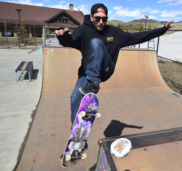 Ryan Carnell, a skateboard coach at the Woodward Copper indoor skate park, flies out of a half pipe, over a half-eaten lunch, Wednesday at the public skate park in Frisco.