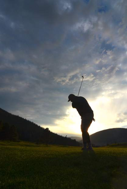 Clark Prinster takes an approach shot on Hole 12 at the Copper Creek Golf Course as the sun dips below the horizon. The Back 9 at the course is heavy on Par 3s of various lengths and difficulties, with elevation changes and grass bunkers.