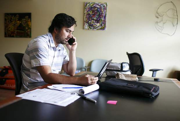 Carlos Santos, who recovered from opioid addiction following a serious spinal cord injury playing high school football, works in his office Monday, Sept. 11, in Dillon.