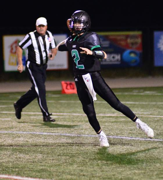 Summit senior quarterback Jake Gillum completes a short pass to running back Dylan Lane on third down Friday night against Steamboat Springs in Breckenridge. Summit won 24-3.
