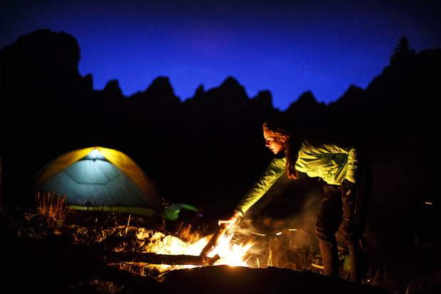 Denver resident Emily Harrell feeds fuel to the campfire in the Eagles Nest Wilderness on a cold Saturday evening near Silverthorne.