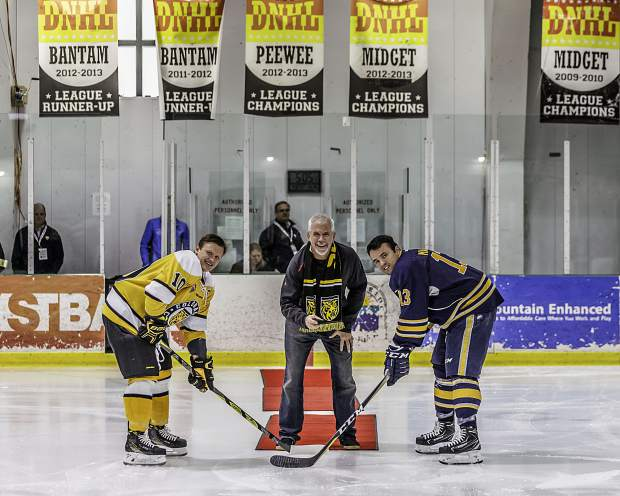 Town of Breckenridge Mayor Eric Mamula, center, drops the ceremonial puck for the beginning of the game.