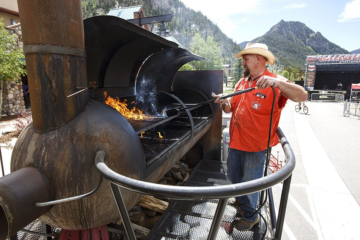 Jay Spurling, of Hugo, Colo., prepares the smoker with a torch ahead of Colorado BBQ Challenge Thursday June 15, in Frisco. The three-day event will feature over 70 BBQers for the competition, along with pig races, music, kids' activities, and food sampling starting at 11 a.m. today and tomorrow on Main Street.