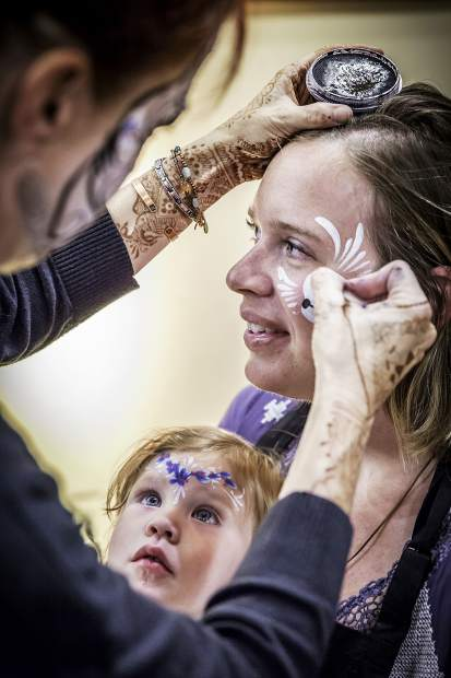 Rhein Weisel watches carefully as Leah Reddell of Face Fiesta paints her mother's face.