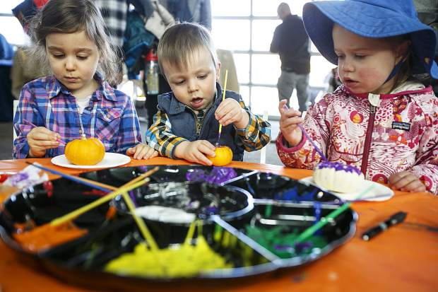 From left; Sorayo Bouanget-Pepe, 4, and her young brother Maxence, 2, and Ilona Bikkal Horne, 2, paint pumpkins during the Fall Festival at the Riverwalk Center Saturday, Oct. 14, in Breckenridge.