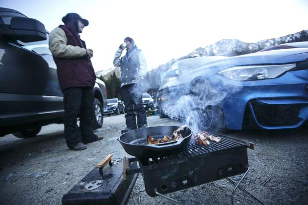 Opening day attendants grill bacon in the parking lot while waiting for the chairlift to operate Friday, Oct. 13, at Arapahoe Basin.