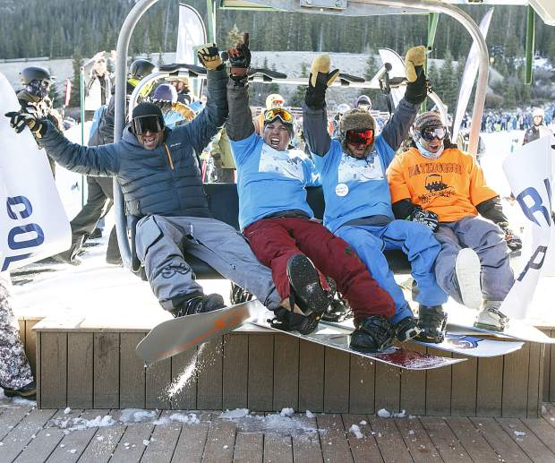 Snowboarders react on the first chairlift ride of the 2017/2018 ski and snowboard season Friday, Oct. 13, at Arapahoe Basin Ski Resort.