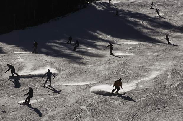 Skiers and snowboarders ride down on High Noon run Friday, Oct. 13, at Arapahoe Basin.