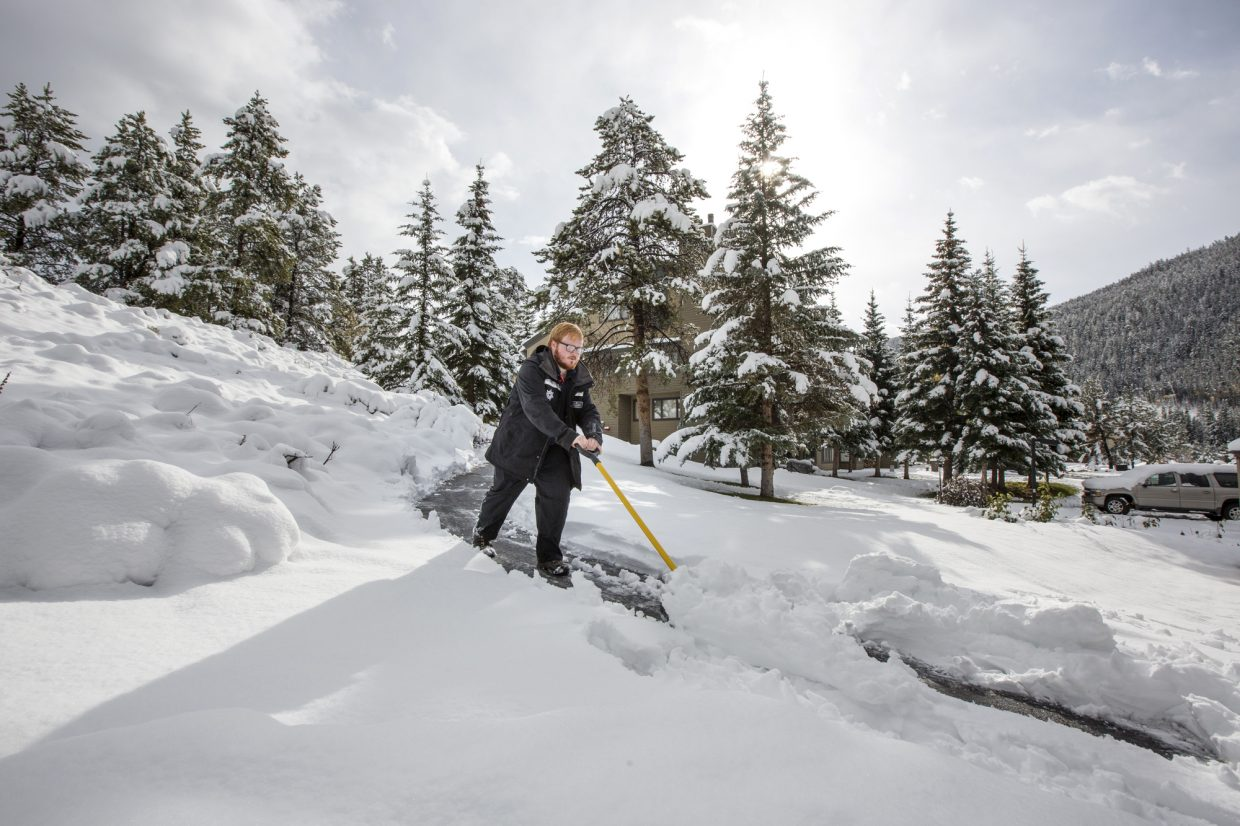 Keystone Ski Resort employee Paul Hamilton, of Orlando, Fla., shovels snow at the Lakeside Village Monday, Oct. 2.