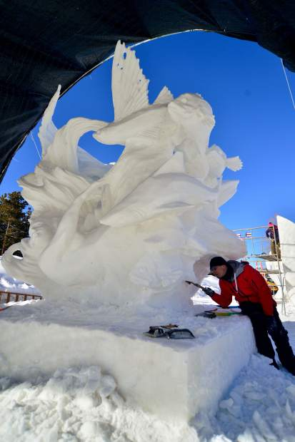 To keep their piece from melting under Wednesday's sun, Zhaoqun du, with Team China, works under cover on a sea-inspired snow sculpture titled