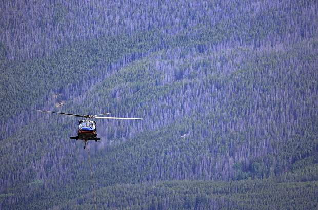A blackhawk helicopter hovers over the mountain pine beetle infested forest Tuesday, July 11, near Keystone.