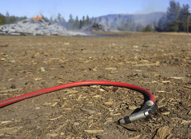 A water hose nearby a burning slash pile Friday, Nov. 3, at the Frisco Peninsula.