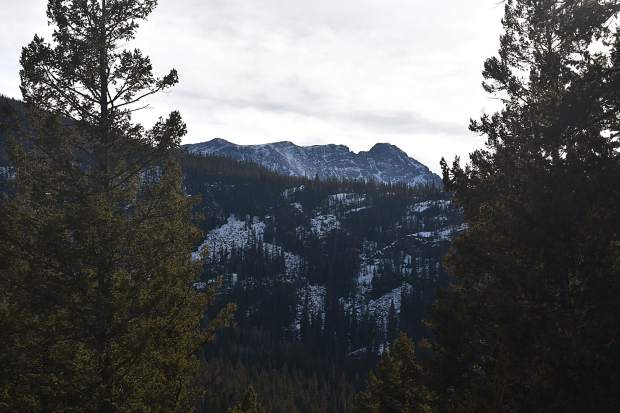 Eagles Nest and a portion of the Gore Range to the south are seen framed through evergreens on the northwestern shore of the Lower Cataract Lake loop trail.