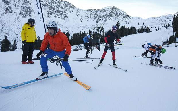 Ski mountaineering competitors transition to downhill mode during the