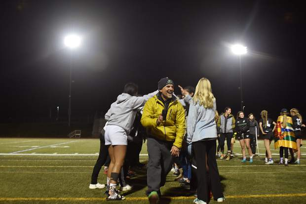Summit Black girls rugby coach Karl Barth runs through a tunnel made by players after Summit Black won their 10th consecutive state title, by the score of 50-7, over Westside Swarm of Denver in Westminster Saturday evening.