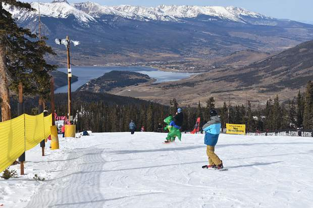 "Erik Richman of Thornton snowboards atop his ""Shredasaurus Rex"" costume Friday morning Nov. 10 as he begins a descent down Dercum Mountain during Keystone Resort's opening day of the 2017-18 season, Lake Dillon in view in the distance."