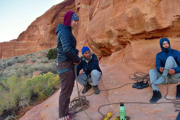 The group at about 6:30 a.m. in the chilly desert as they step into harnesses, put on their respective climbing shoes and rope into the system.