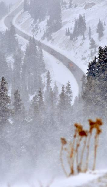 A snowplow carves its way down U.S. 6 after crossing the Loveland Pass on Saturday. The Colorado Department of Transportation put into effect and later lifted traction-law requirements along the route. Those restrictions could be reinstated if conditions worsen.