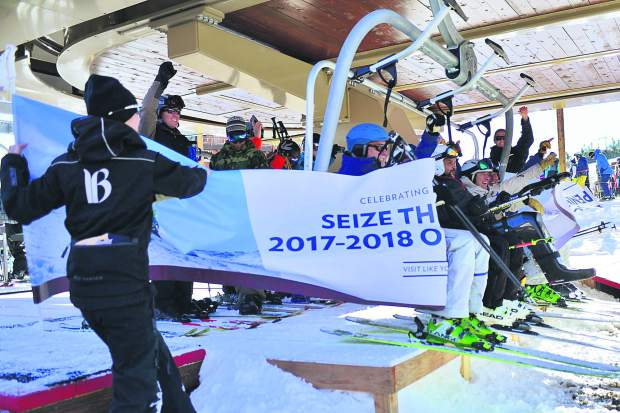 "Skiers riding first chair lift of the 2017-18 season break through a banner that reads, ""Seize the Season – 2017-18 Opening Day,"" Friday at Breckenridge Ski Resort. The Summit County ski resort is now running with a limited amount of terrain and will remain open daily through the end of April."