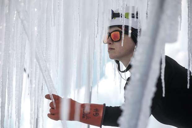 Glenys Hunt carefully harvests icicles during the construction for the Ice Castle on Dec. 20, 2017, at the site in Dillon Town Park.
