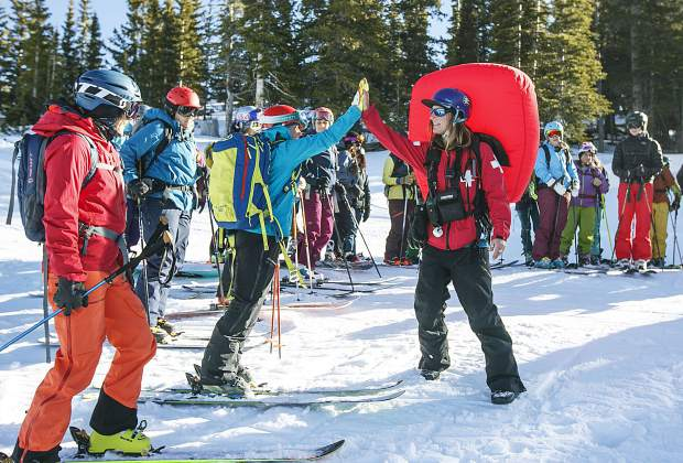 Copper Mountain Ski Patroller Kylie Petras, far right, high fives a group member during the S.A.F.E. A.S. clinic Saturday, Dec. 2, at the resort.