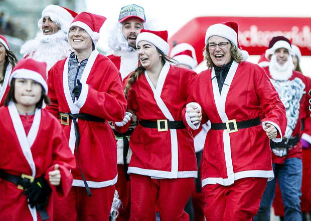 Holiday enthusiasts dressed as Santa Clauses take part in the Race of the Santas Saturday, Dec. 2, on Main Street in Breckenridge.