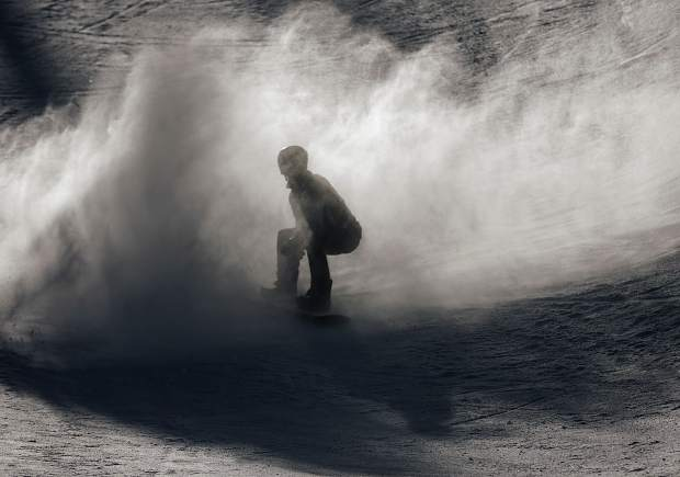 A snowboarder rides out his sprayed snow at the of the superpipe competition Friday, Dec. 15, at Breckenridge Ski Resort.