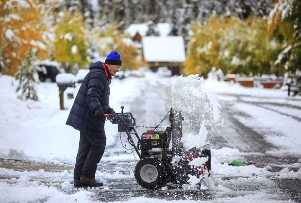 Summit County resident Ron Gilligan clears snow off his driveway in the Summit Cove neighborhood Monday, Oct. 2 near Dillon, Colo.