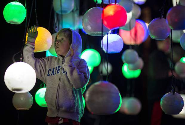 A young visitor interacts with suspended globes during BreckCreate's WAVE festival at the Blue River Plaza Thursday June 1, 2017, in downtown Breckenridge. The exhibition of cutting-edge works of contemporary public art featuring illuminated sculptures and projections will be on display until Sunday night.