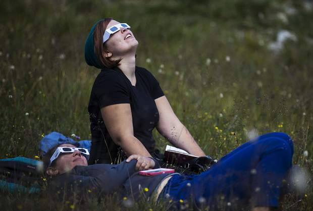 Lily Becknell, right, and Amanda Wolff, both who traveled from Denver, to view the solar eclipse through the goggles Monday, Aug. 21, at Arapahoe Basin.