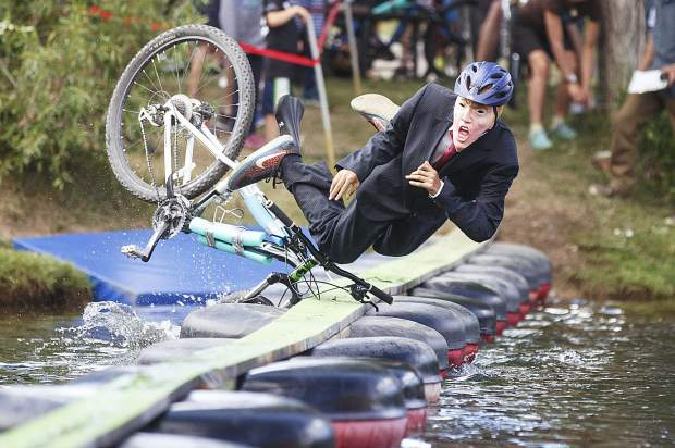Jake Bell, with mask, of Breckendridge, trips from the bike off the floating plank walk in the Funkadelic Pond Crossing Challenge event Sunday, June 24, at the Dredge Pond in Breckenridge.