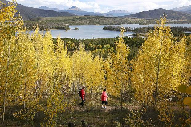 Signs of autumn appear early in Summit County as Paul, left, and Judy Burnham, of Madison, Wis., enjoy a late afternoon hike Tuesday near the Dillon Reservoir.