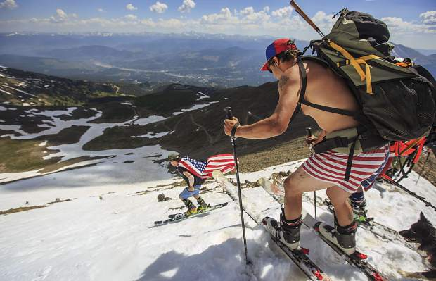 Matty Baldwin, right, and other skiers make a descent into Fourth of July Bowl on July 4, 2017 on Peak 10 near Breckenridge. The north facing bowl is known to hold snow for longer time due to high elevation with its summit at 13,633 feet, attracting at least 200 skiers and snowboarders at the mountain at a time to celebrate the holiday.