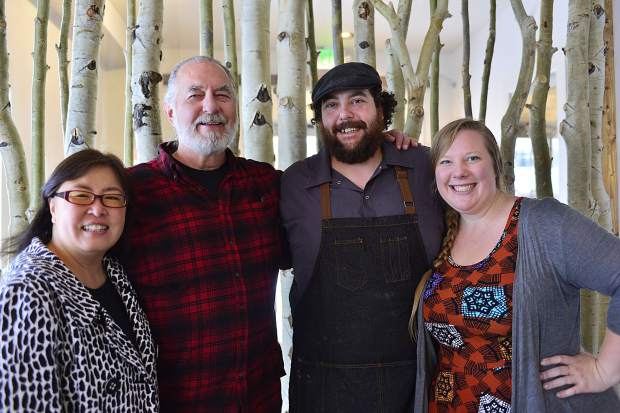 "From left, Corinna Jang, Chris Litsey, Chef Samir Mohammad and Rachel Firestone pose for a photo next to the aspen wall inside Artisan 206. Litsey and Jang are Mohammad's ""adopted parents,"" though all of them say he adopted them, not the other way around."