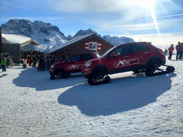 A pair of SUVs with snow track tires are in view at the top of Madonna di Campiglio.