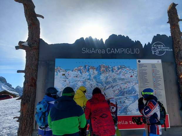 Skiers and snowboarders check the Ski Area Campiglio map.