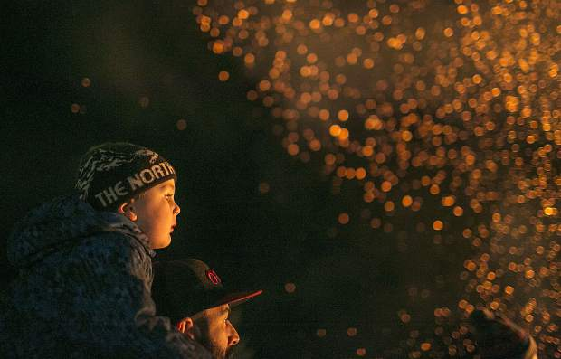 Nico Tripodi, 3, watches the bonfire from the shoulders of his father, Matt, of Denver, during the Spontaneous Combustion event Saturday, Jan. 20, at the Frisco Marina.